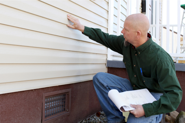 Siding Inspection by a worker