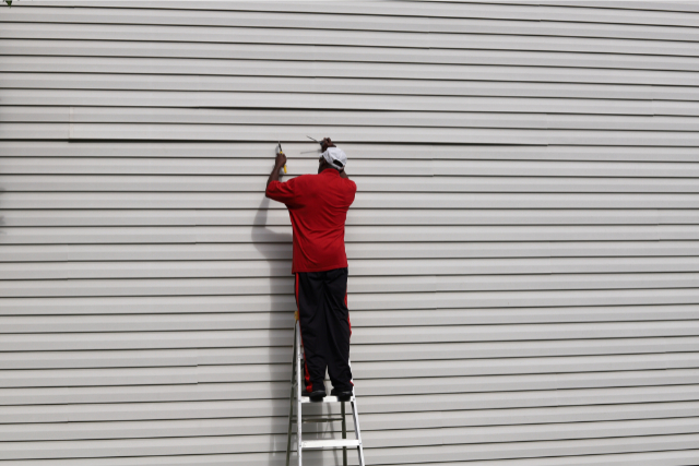 Siding Repair by a worker on a ladder