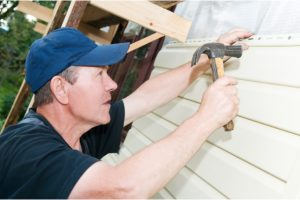 Siding Repairs by worker with a hammer